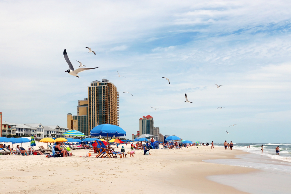Alabama Gulf of Mexico beach life. Marine landscape with beach line homes and hotels, beach umbrellas, people and flying birds on a foreground. Alabama Gulf Shores State park and beach, USA.