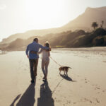 retired couple walking on beach with dog