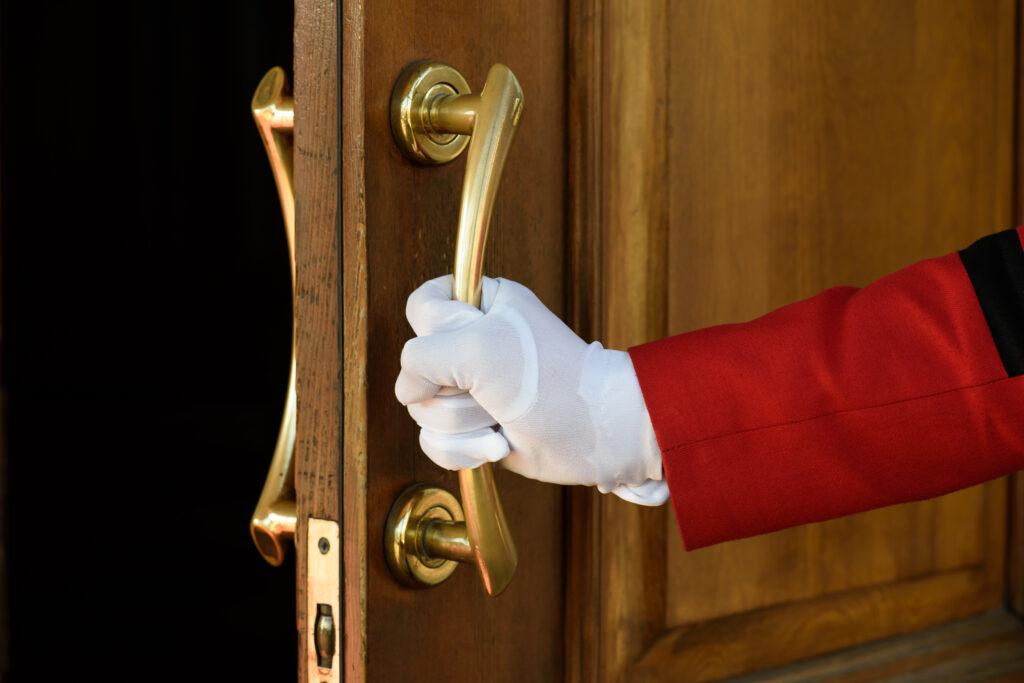 Doorman opens hotel room door.