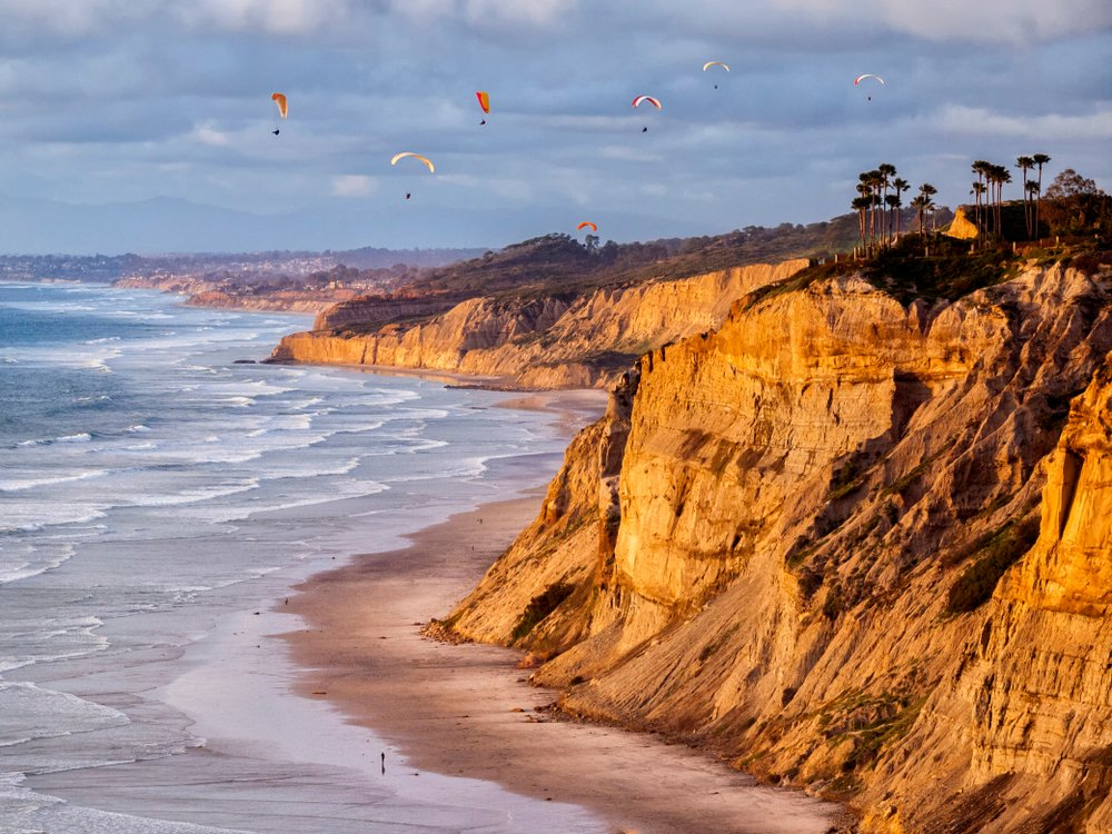 USA, California, La Jolla. Paragliders float over Black's Beach in late afternoon