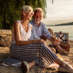 happy woman and man couple over aged 50 picnic by river