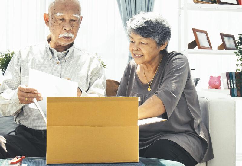 senior man and woman opening gift box at home