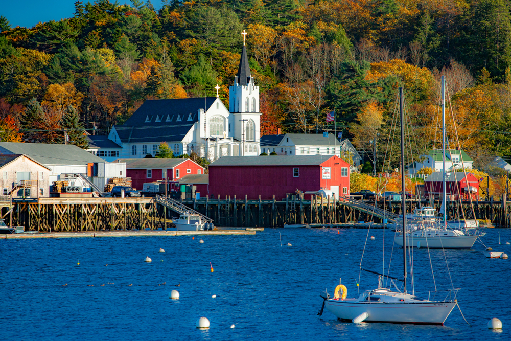 Boothbay harbor, Maine - 10/22/2006: Our Lady Queen of Peace catholic church on the shore of Boothbay harbor, Maine. Sail boats moored in harbor.