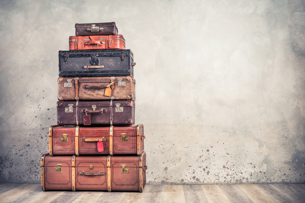 Vintage classic outdated trunks luggage with tags, old antique leather suitcases tower front concrete wall background. Travel baggage concept. Retro style filtered photo
