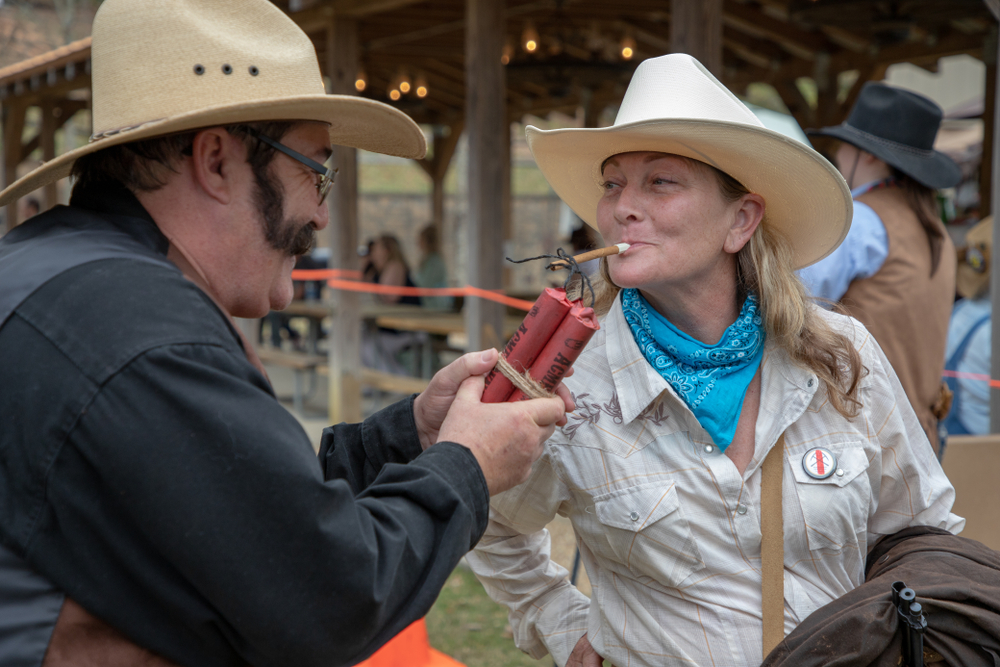 Villa Rica, GA / USA - April 13, 2019: Cowboy Festival 2019 at Pine Mountain Gold Museum. A cowgirl lighting dynamite with cigarette, while cowboy holds the dynamite.