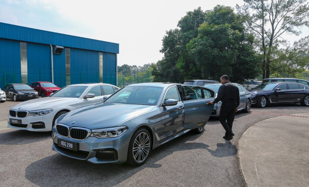 Hertz services with chauffeur driving luxury BMW car.