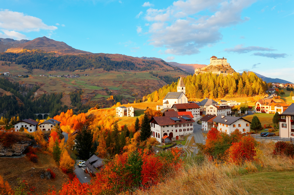 Autumn scenery of Tarasp Castle perched on a hilltop and village houses scattered in the valley with beautiful fall colors under blue clear sunny sky in Scuol, Grisons (Graubunden), Switzerland