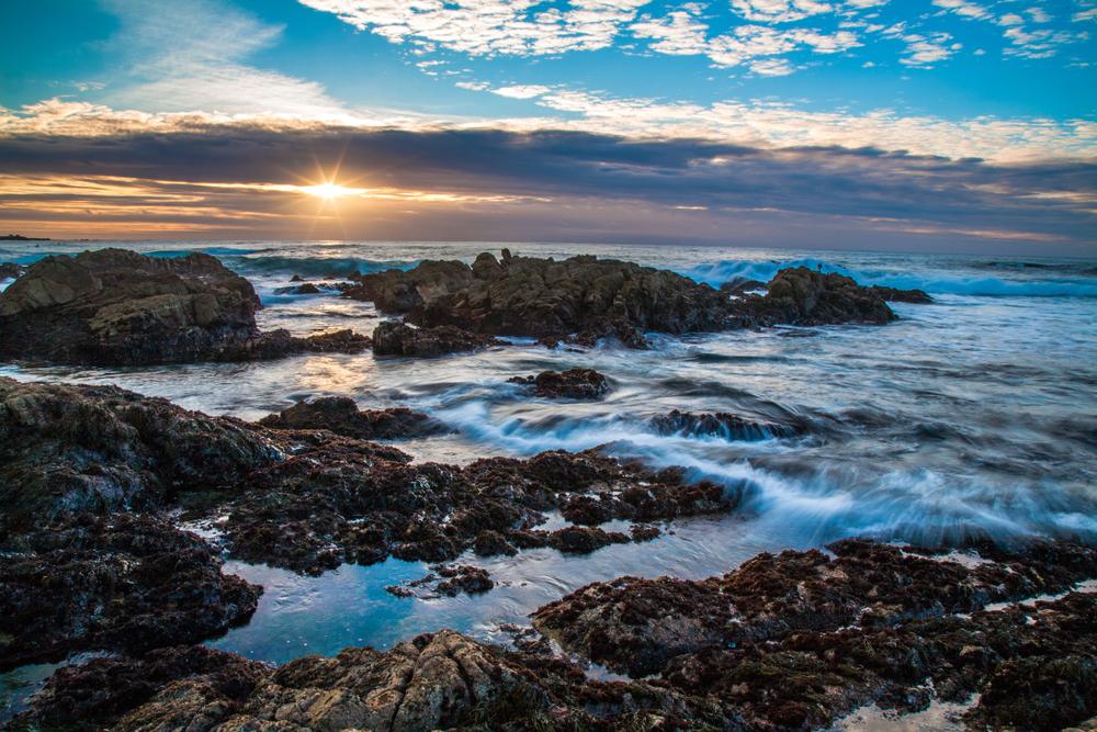 Sunset and waves on rocks at Asilomar State Beach, Monterrey California
