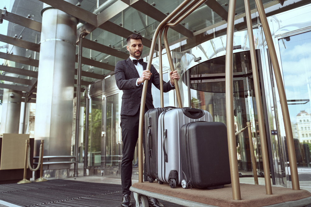 Tall handsome hotel worker having his back to hotel entrance pulling a heavy luggage trolley delivering guests suitcases