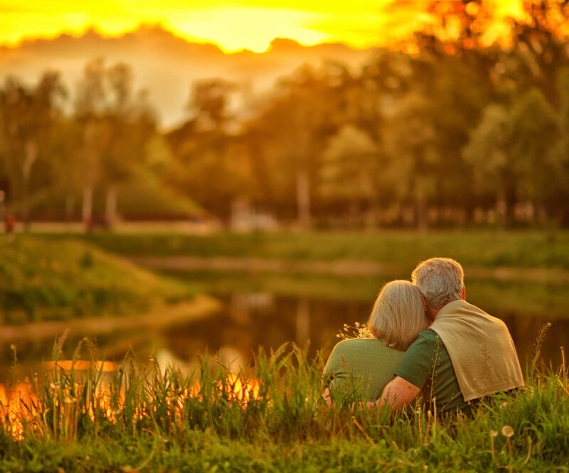 older couple sitting together watching the sunset