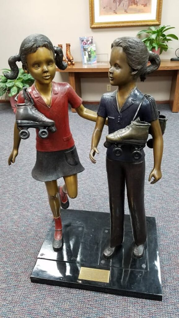 Sculpture of girls with roller skates slung across their shoulders at National Museum of Roller Skating.
