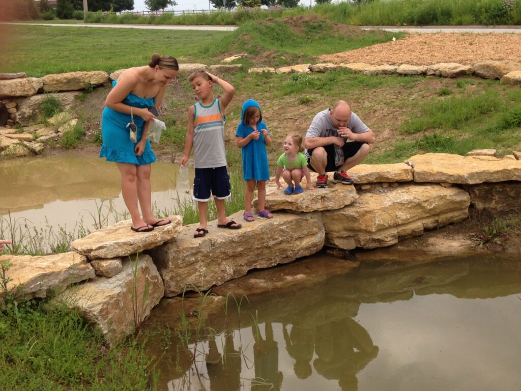 family catching tadpoles at George Owen Nature Park in Independence, MO