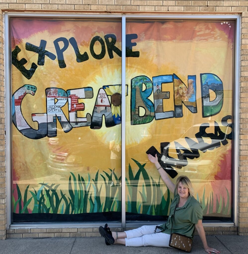 The author posting next to a Great Bend Kansas sign.