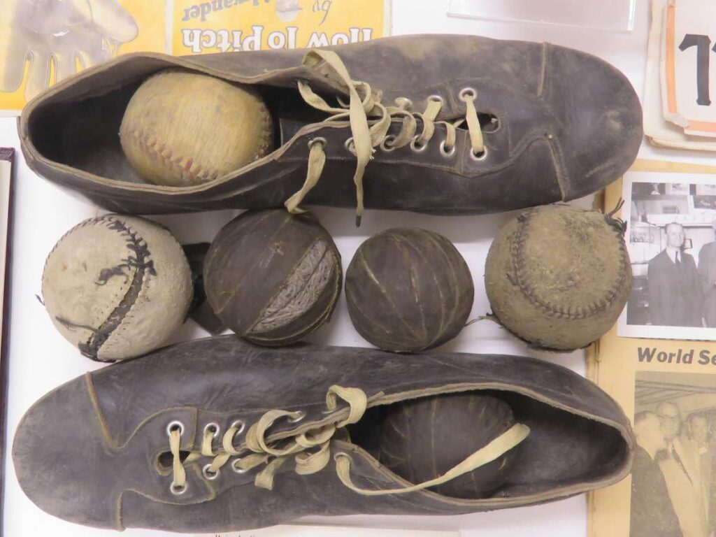 Shoes and baseballs in the Grover Cleveland Alexander exhibit at baseball museum.