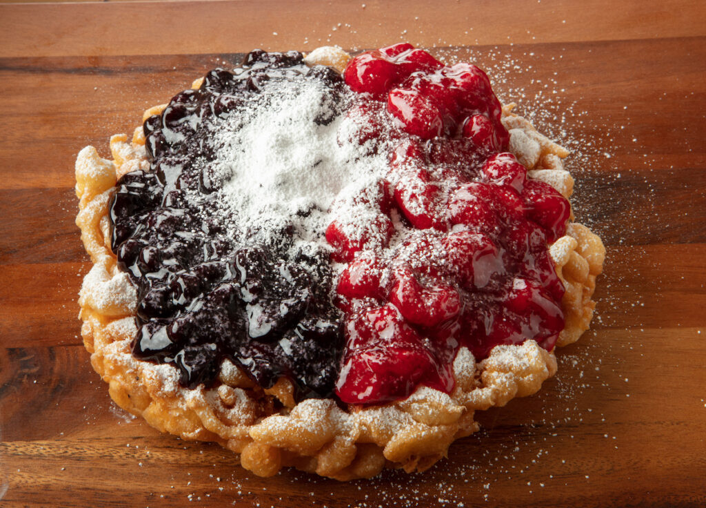 A funnel cake with berries.