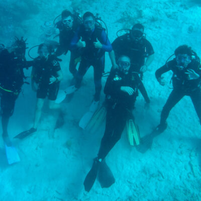 Underwater scuba divers pose for underwater group picture.