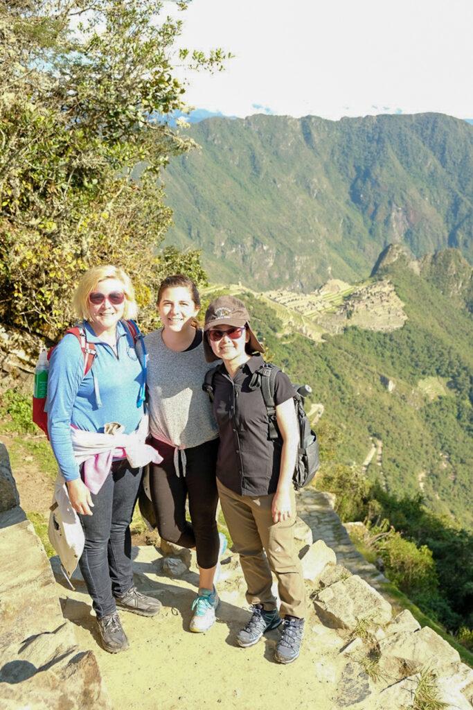 Family takes photo standing on the Intipunku trail in Machu Picchu.