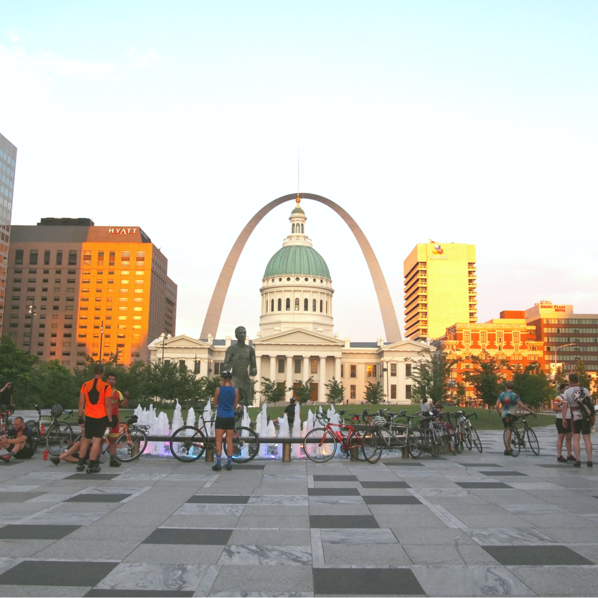 Bicyclists near the Gateway Arch and the Mississippi River.