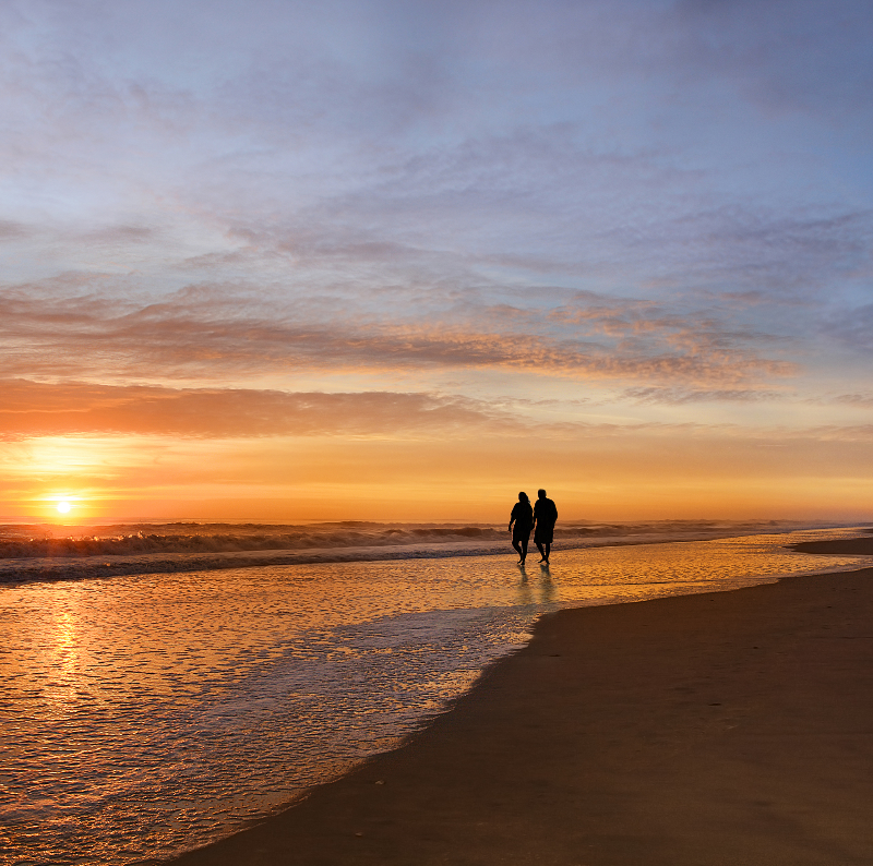 older couple walks on the beach of North Carolina's Outer Banks