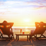 Couple relaxing on beach at sunset