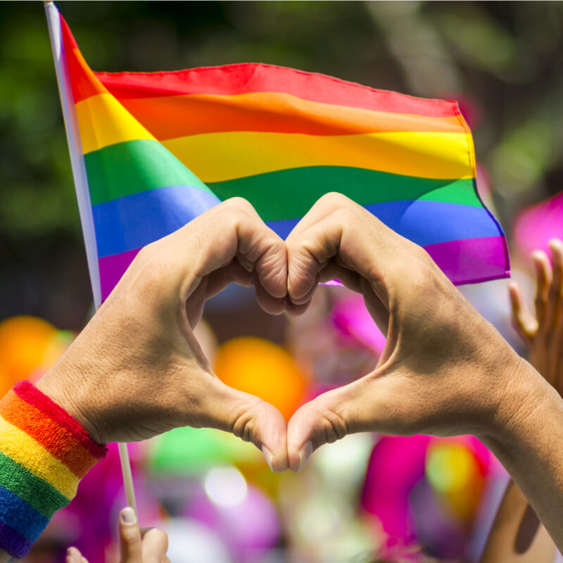 Hands in heart formation at PRIDE parade.