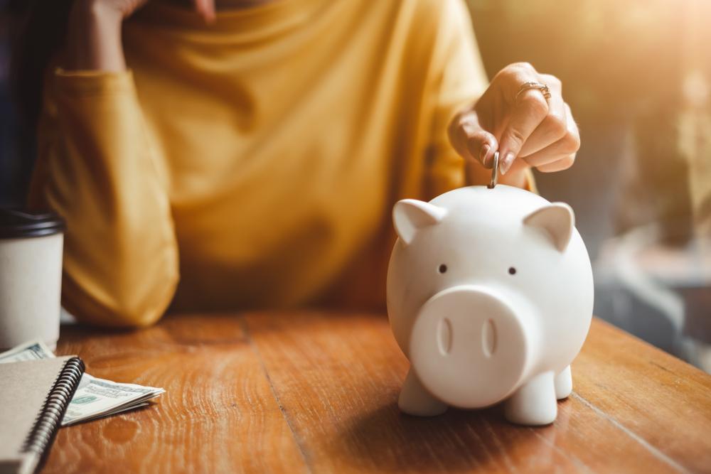 Mano de mujer poniendo moneda de dinero en alcancía para ahorrar dinero.