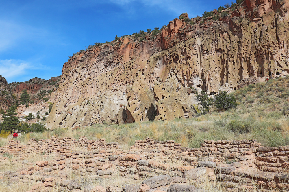 Part of the Tyuonyi ruins of the ancestral Pueblo people by the cliffs along the main loop trail in Frijoles Canyon at Bandelier National Monument near Los Alamos, New Mexico against a blue autumn sky