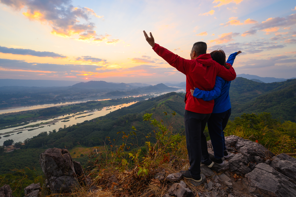 Senior healthy couple hiked the hill to see the sunrise view over Mekong river at Phu Pha Dak hill in Nong Khai, Thailand