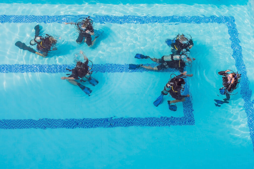 Diving instructor and students. Instructor teaches students to dive in a swimming pool.