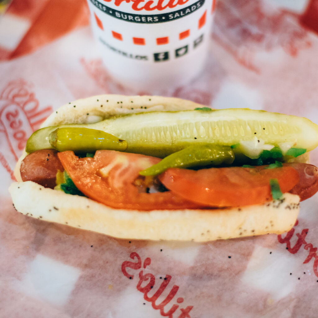 Loaded Portillo's hot dog with fresh vegetables.