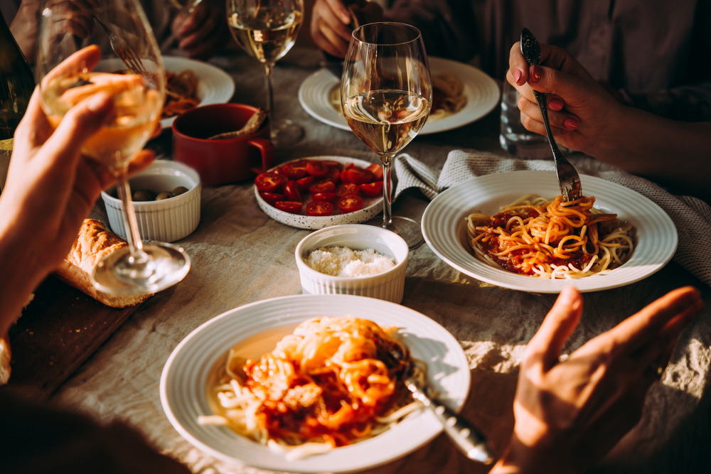 Friends having a pasta dinner at home or at a restaurant.