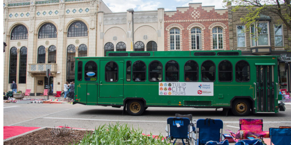 Vintage trolley bus and local architecture with people in downtown Holland, Michigan.