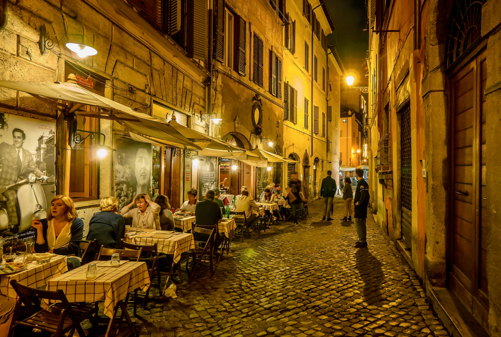 A residential street in Rome, Italy, where people are dining outdoors at a small neighborhood restaurant on an old cobblestone street at night.