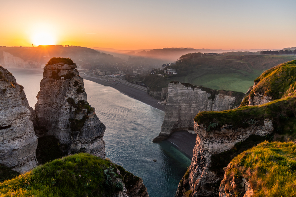 Landscape photo of the sun rising behind steep cliffs in the early morning near a foggy, misty coastal village with grass in the foreground. Shot in Etretat, Normandy, France.