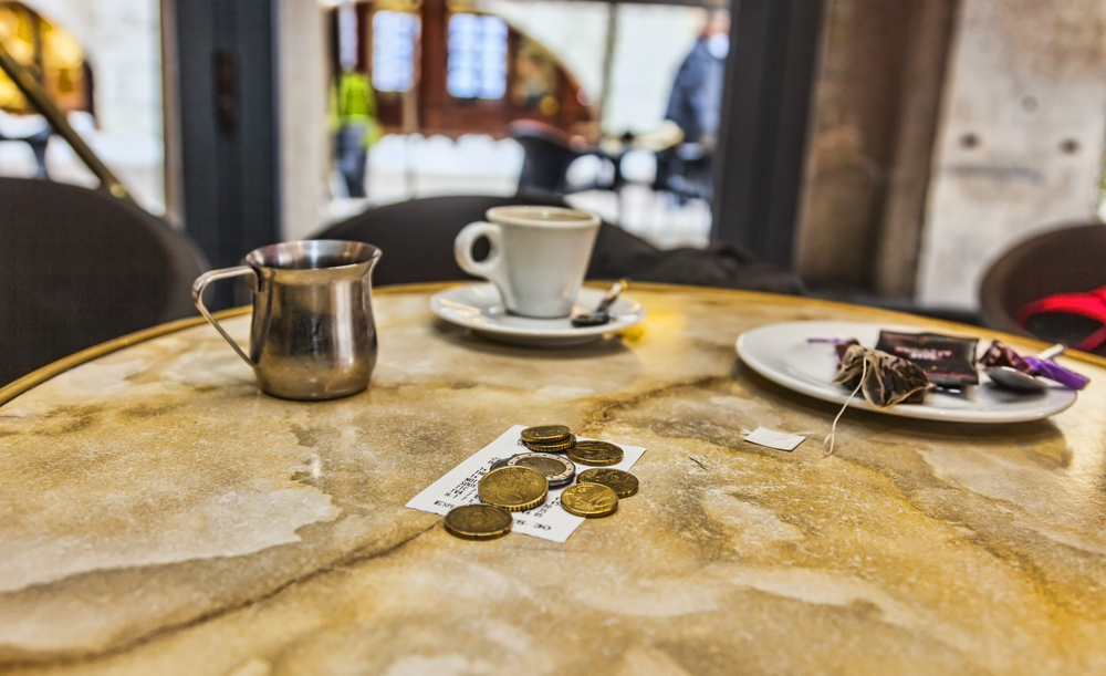 Few coins and the bill on a coffee table after the clients have left.