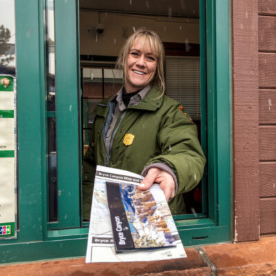Female blond National Park Ranger hands out brochure through window at Bryce National Park, Utah