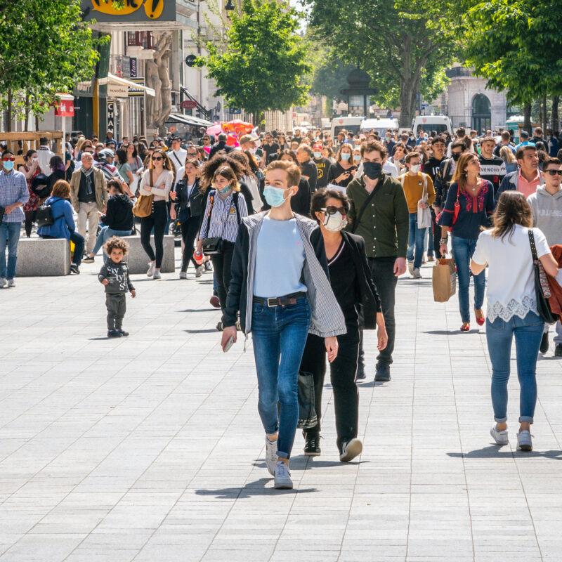 People walking down the street wearing face masks in Lyon France.