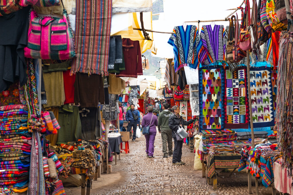 European Travellers walking and shopping local Peruvian products, Pisac market, Scared Valley, Cusco, Peru