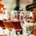 White wine pouring into glasses, closeup.