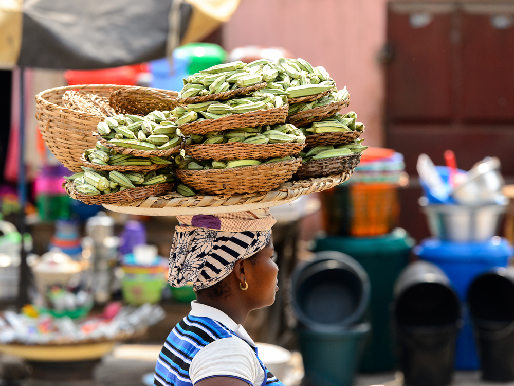 Benin woman carries baskets of produce on her head