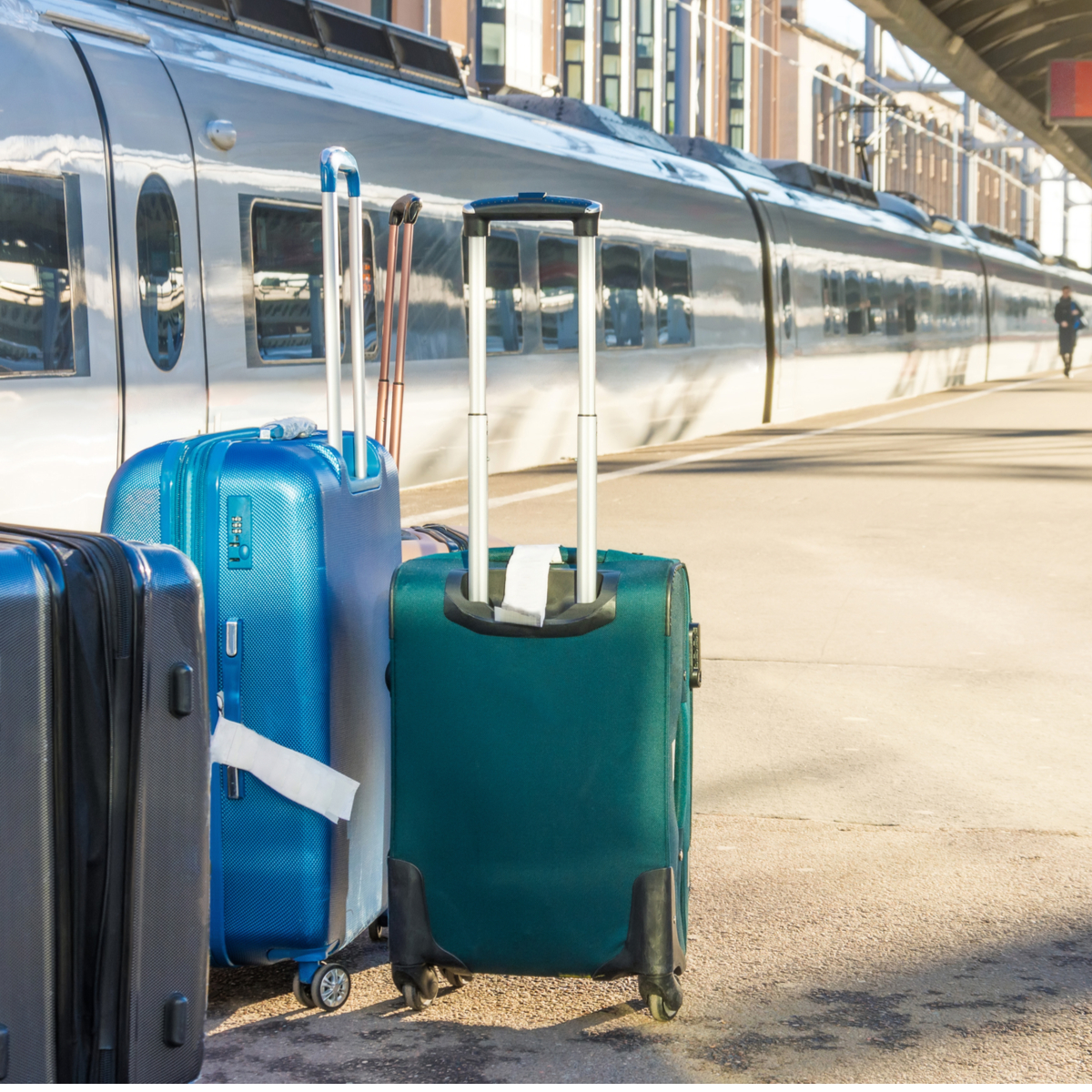 Rolling suitcases at a train station.
