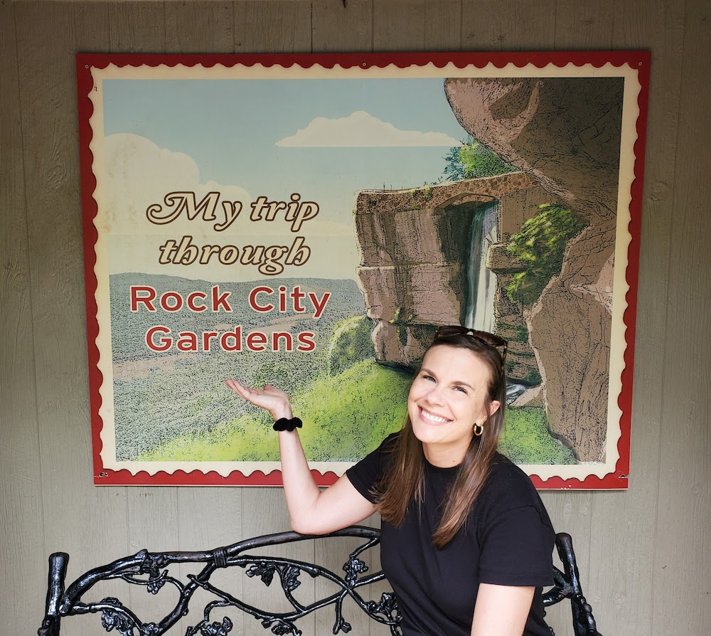 Laura Ray smiling in front of illustrated sign of Lover's Leap My Trip through Rock City Gardens'