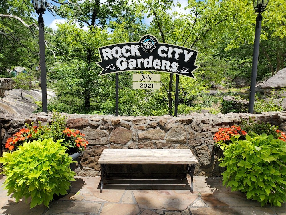 Rock City Gardens sign over bench between two ferns