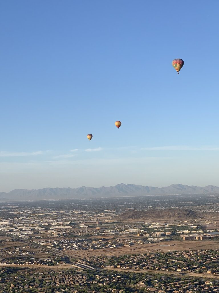 Hot air balloons floating high on the horizon in Scottsdale, Arizona.