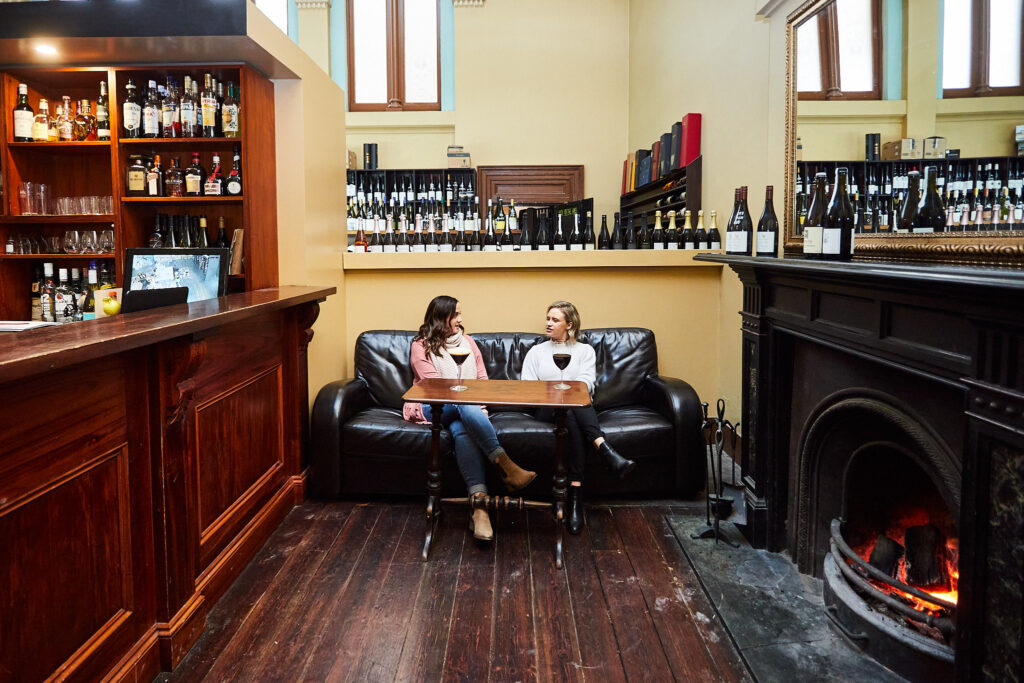 two women drinking red wine on a black leather couch at a winery
