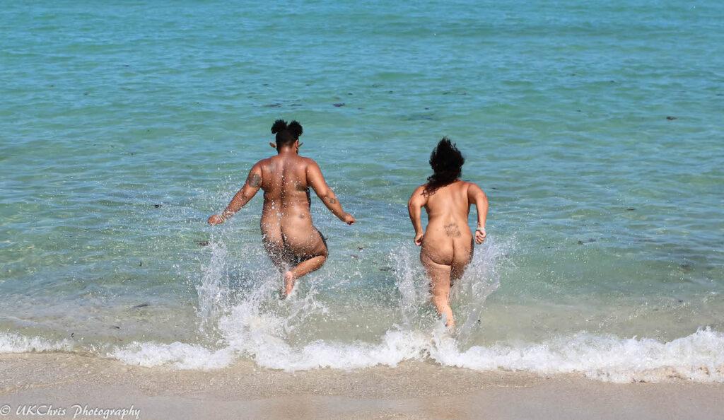 Naturist couple running into the water on beach.