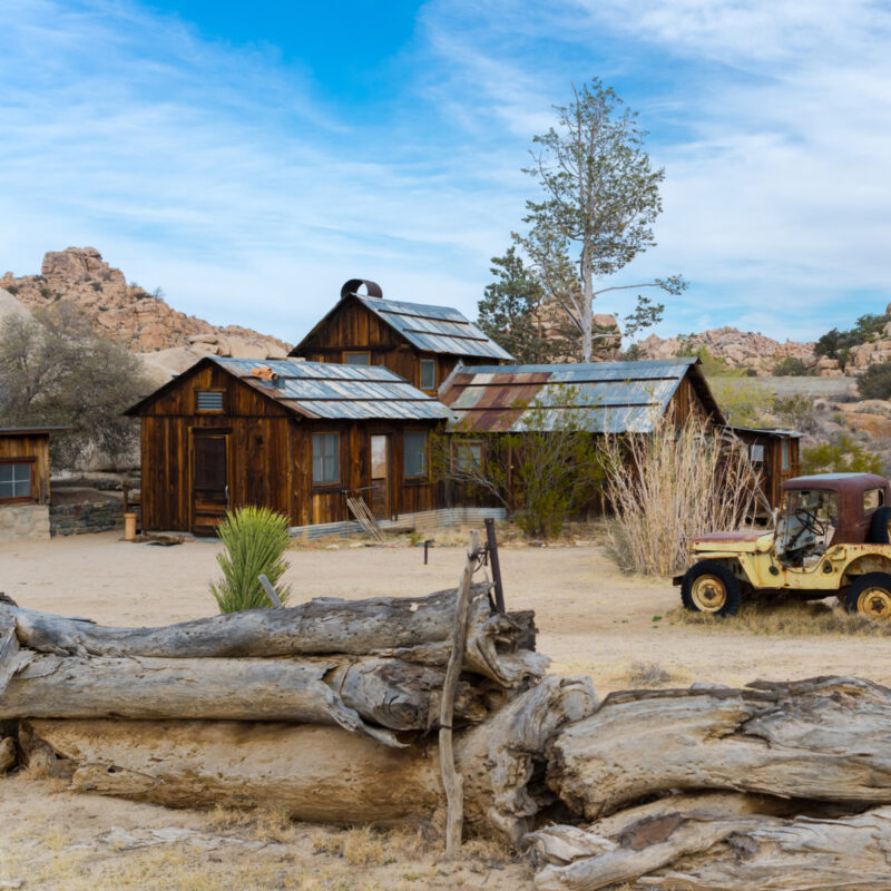 The wooden Key's Ranch house with offroad vehicle towing a trailer in front at Joshua Tree National Park.