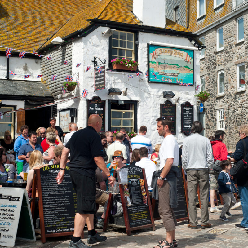 The Sloop Inn traditional 14th century pub busy with holidaymakers sitting outside.