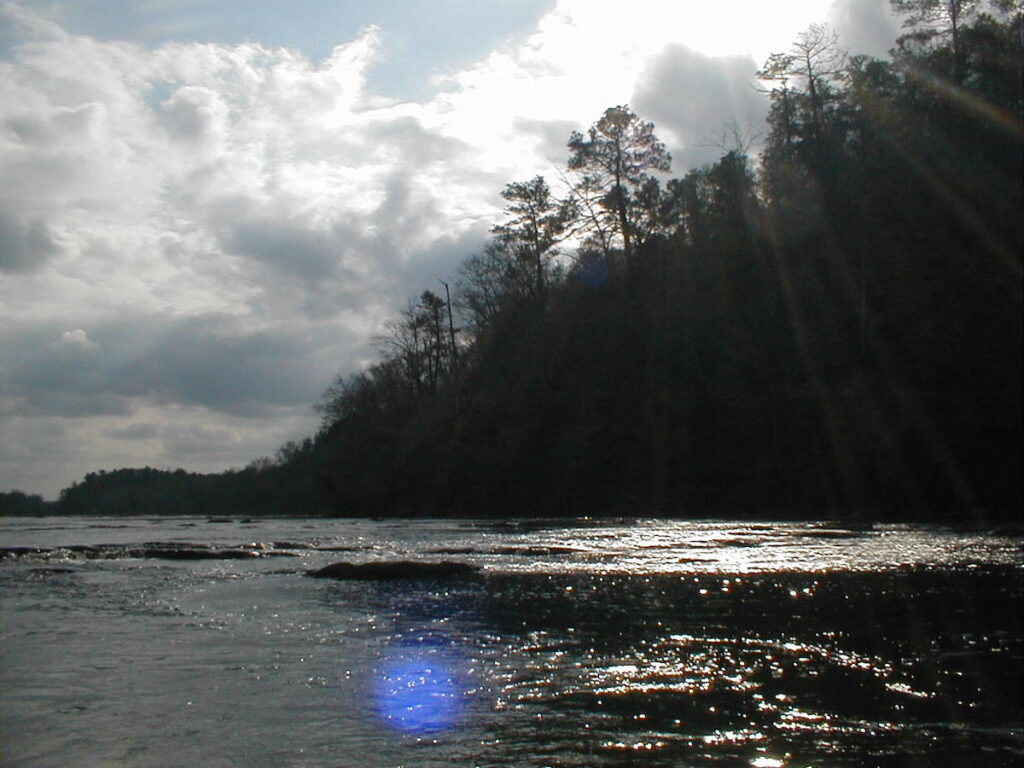 The sun shimmers on the water of the Tallapoosa River.