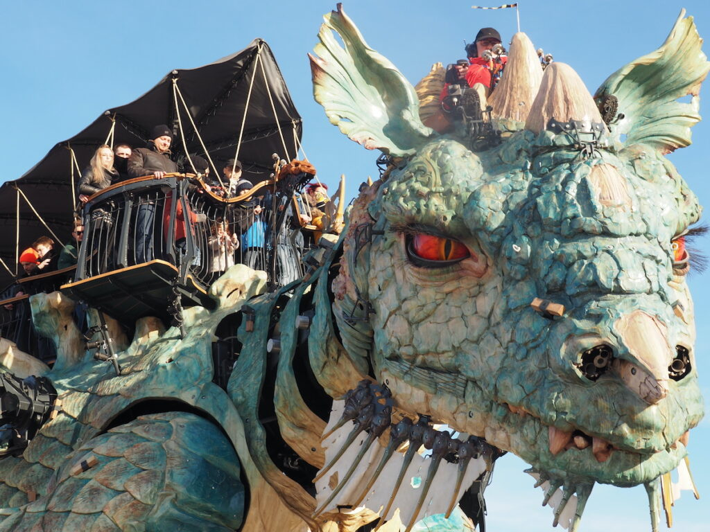 The Calais Dragon close up of face and visitors up on its back.